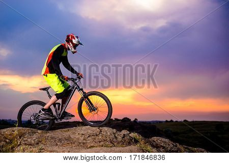 Professional Cyclist Riding the Bike on the Rock at Sunset. Extreme Sport Concept. Free Space for Text.