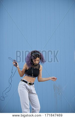 interracial teenager listening to music and dancing with big headphones on a blue background