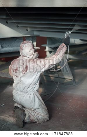 Painting of metal structures hand man in protective clothing