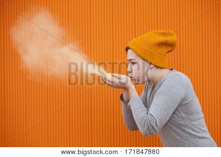 teen woman blowing a colored dust cloud on an orange background