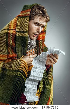 Man covered in blanket reads to instructions. Photo of sick man suffering cold and flu virus. Health care concept