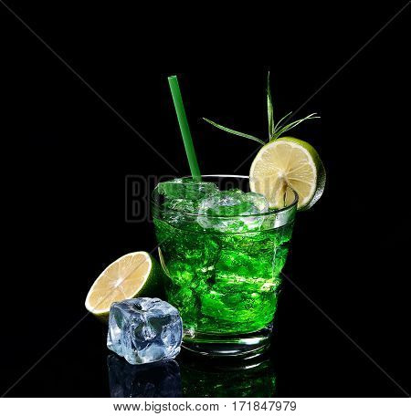 Green tarragon drink with ice cubes, lime on a black  background