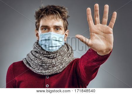 Stop - virus! Sick man in protective mask gesturing stop. Healthcare concept