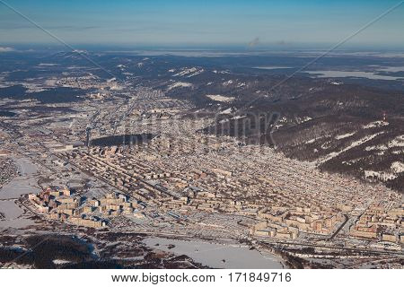 View from above of the industrial center of the Urals city of Miass in winter, surrounded by winter mountains.