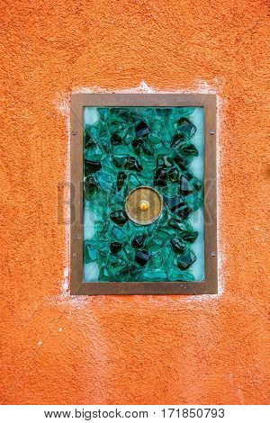 Picturesque green door  bell with glass mosaic and round button on the famous island Burano, Venice, Italy.