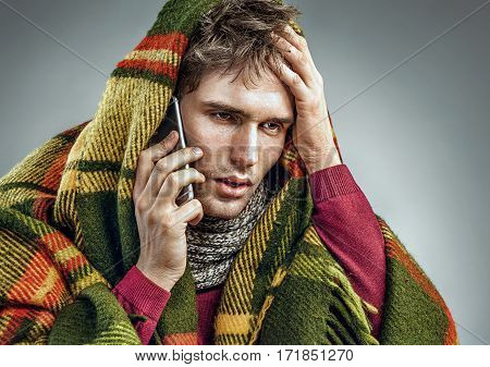 Unhealthy man wrapped in blanket with high temperature calling on the phone. Man suffering cold and winter flu virus