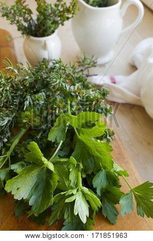 A bunch of freshly picked herbs on a chopping block.