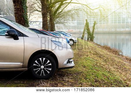 STRASBOURG, FRANCE - FEB 2017: Rows of cars parked in front of Ill river in Strasbourg with the European Parliament building seen in the background