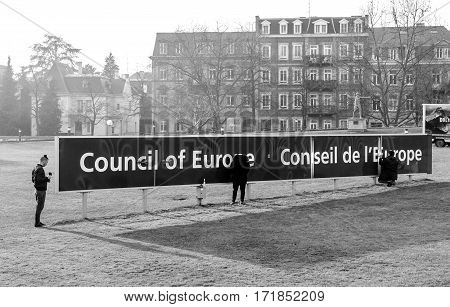 STRASBOURG FRANCE - FEB 2 2017: Workers taking care of the Council of Europe Conceil de Europe blue signage in front of the international organisation focused on promoting human rights democracy and the rule of law in Europe