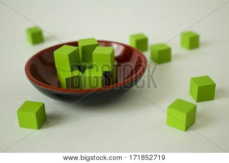 Green cubes scattered in and around a dish.