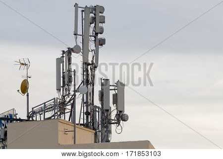Group of cellular phone antennas on a building roof.