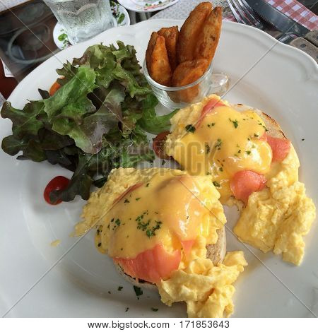 Eggs Benedict with smoked salmon top with fresh herbs and hollandaise sauce serve with green salad and french fries with blur background poached egg top view