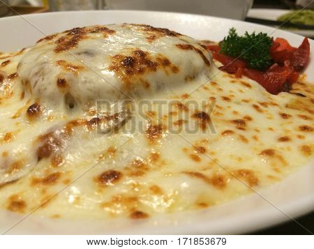 Stylist food Close up homemade Japanese beef or pork curry severe with red radish and top with melt cheddar cheese on white plate in restaurant. healthy vegetarian food. Italian food concept
