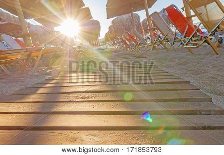 Sunbed, straw umbrella on beautiful beach background with burning sun