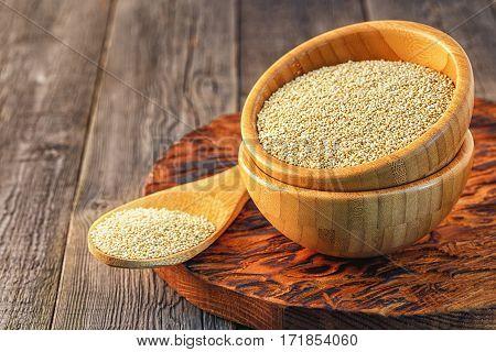White quinoa in a wooden bowl, selective focus.