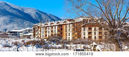 Wooden chalet, houses and snow mountains landscape panorama in bulgarian ski resort Bansko, Bulgaria