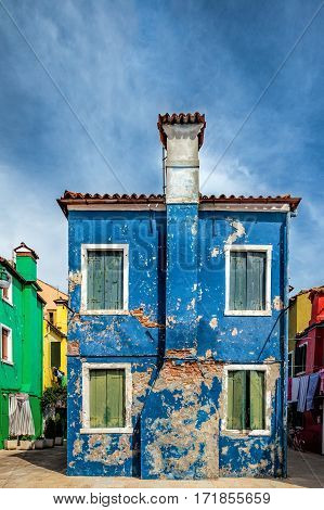 Lovely blue building with bricks showing under the paint in Burano Island, Italy.