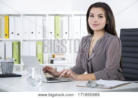 Side View Of Smiling Woman In Gray In Office