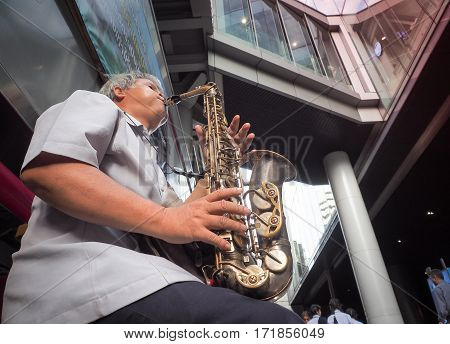 BANGKOK, THAILAND - DECEMBER 16, 2016 : The musician plays saxophone for donations on silom street, This road is the center of business in Bangkok.