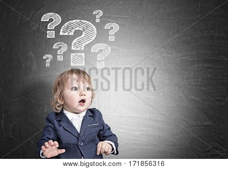 Portrait of an adorable little boy wearing a suit and standing with an open mouth near a blackboard with question mark sketches. Mock up.