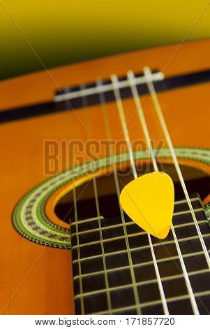 Closeup detail of a classic guitar and yellow plectrum over yellow background