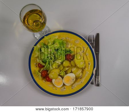 top view on salad with potatoes cherry tomatoes and eggs chipped on a yellow plate white wine in wineglass vegetarian dish