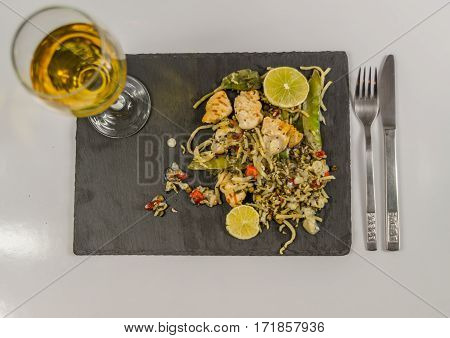thai chicken with basmati rice coconut sauce on black stone plate with cutlery white wine in a wineglass oriental food