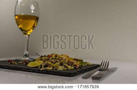side view on thai chicken with basmati rice coconut sauce on black stone plate with cutlery white wine in a wineglass oriental food