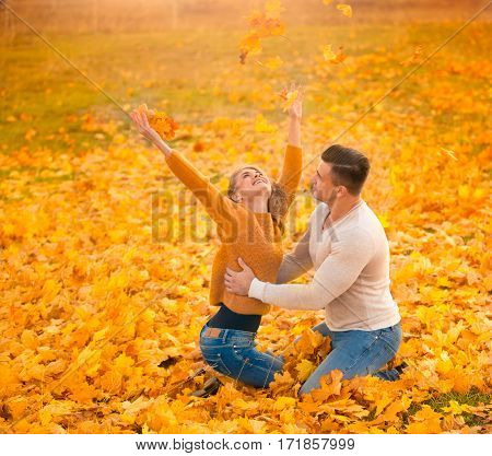 Youn woman and man couple playing in autumn park