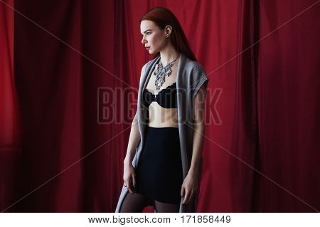 Beautiful red-haired girl in black lingerie on red background looking at the camera. Fashion photography. Bright appearance. Red hair