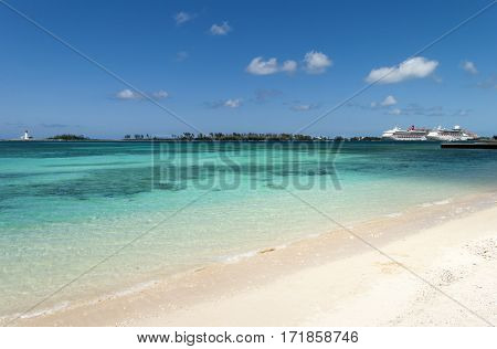 The view of an empty Nassau city beach with cruise liners and Paradise Island lighthouse in a background (The Bahamas).