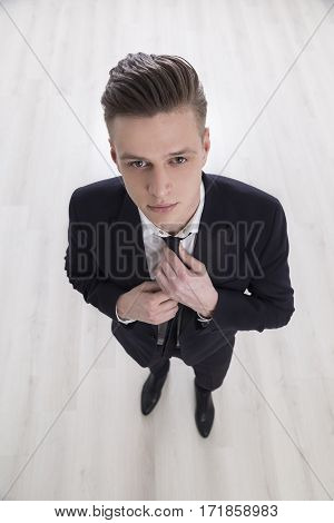 Top view of a young and handsome businessman adjusting his tie before an important talk with his boss about promotion.
