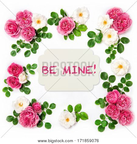 Rose flowers with green leaves. Valentines Day. Floral flat lay background with white paper tag. Sample Text Be Mine