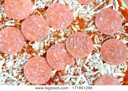 Raw unready pizza with sausage and cheese as background top view closeup