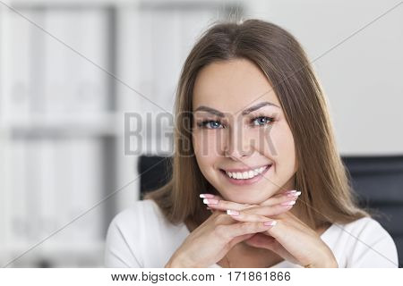 Close up of a cheerful businesswoman smiling broadly and looking at the viewer. She has her hands under her chin. Concept of satisfaction.
