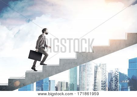Side view of a bearded man carrying a suitcase and going up the stairs. There are skyscrapers in the background and a cloudy sky.