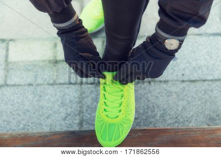 Urban jogger tying running shoes in the park.
