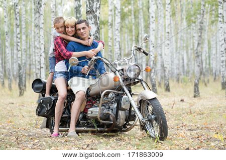 Family on a motorcycle in a birch grove.
