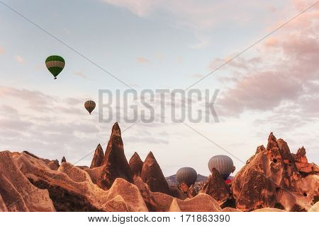 Hot air balloon flying over rock landscape at Cappadocia Turkey. Valley, ravine, hills, located between the volcanic mountains in Goreme National Park.