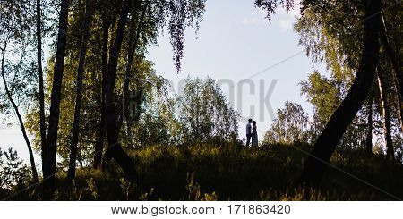 silhouette of kissing couple on a hill a couple in love in a beautiful location sunset lighting