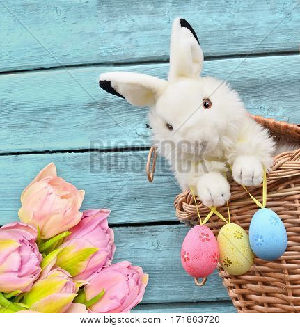 rabbits in the basket with Easter eggs and flower on wooden background