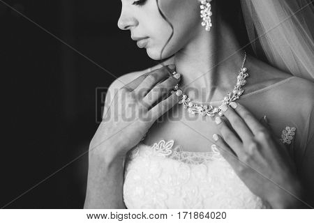 beautiful bride in a white dress holding a necklace