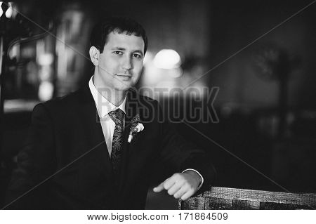 The groom in a suit on a dark background