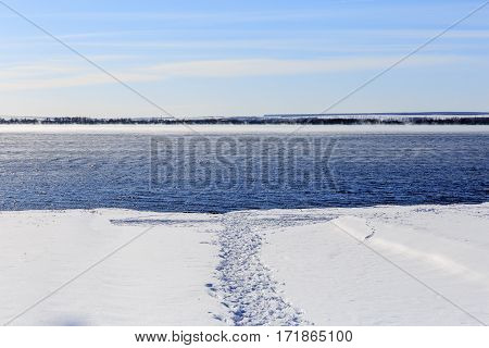 Trodden path in the snow to the water. Not frozen lake in the winter. Steam rises above the water. Bright blue sky. Free blank copy space for text.