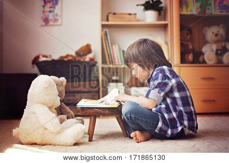Cute Little Child, Preschool Boy, Reading A Book To His Teddy Bears At Home