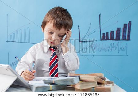 Young Boy, Talking On The Phone, Writing Notes, Money And Tablet On The Table