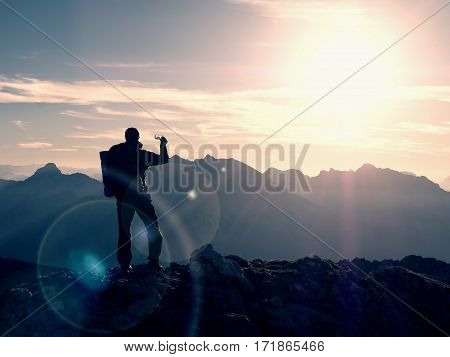 Hiker Takes Selfie Photo. Man With Big Backpack And Poles Walk On Alpine Mountain
