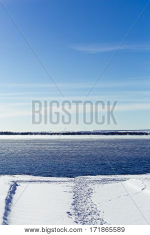 Trodden path in the snow to the water. Not frozen lake in the winter. Steam rises above the water. Bright blue sky. Free blank copy space for text. Vertical image.
