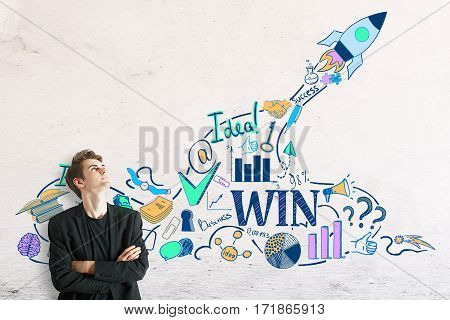 Young businessman on concrete background looking at creative space ship sketch. Start up concept