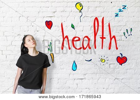Thoughtful young girl on brick background with heart sleep water and healthy food doodles. Health concept